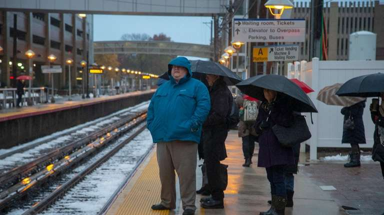 Commuters dodge the rain at the LIRR station
