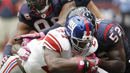 Giants running back Brandon Jacobs goes over the