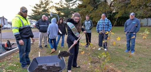 Girl Scout Ashley Tarricone shovels compost around a