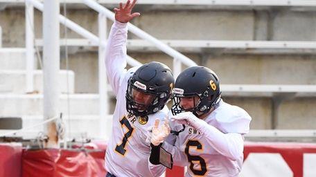 Xavier Arline, left, celebrates his touchdown run with