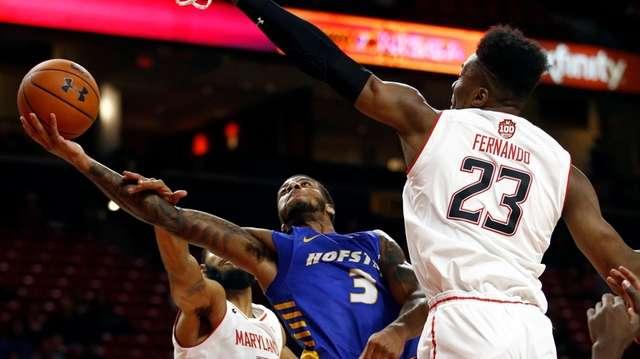 Hofstra guard Justin Wright-Foreman, center, is fouled by