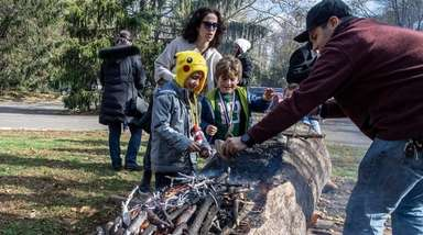 Children learn how Native Americans carved logs by