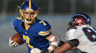 Jordan Delucia #7 of Kellenberg, left, rushes for