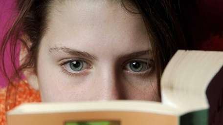 A young woman reads a book.