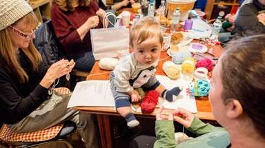 Isaac Kantor, 4 months, helps his mother Kim,