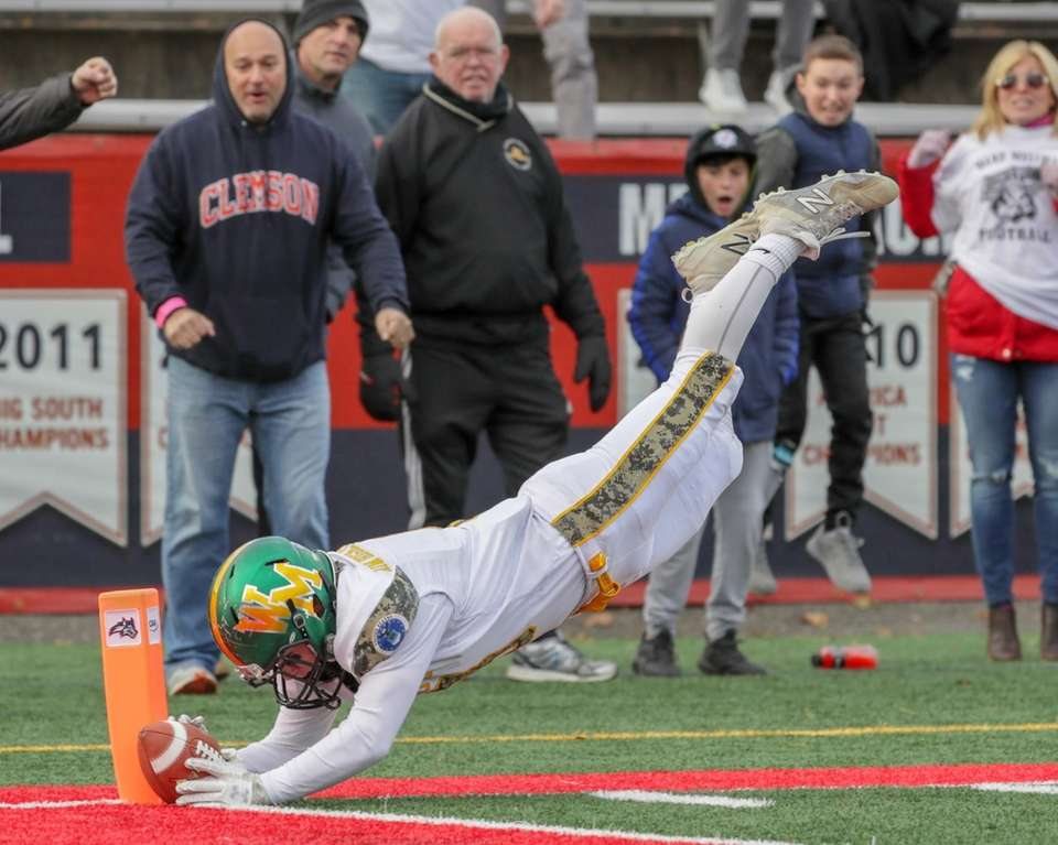 Jack Gillen of Ward Melville dives over the
