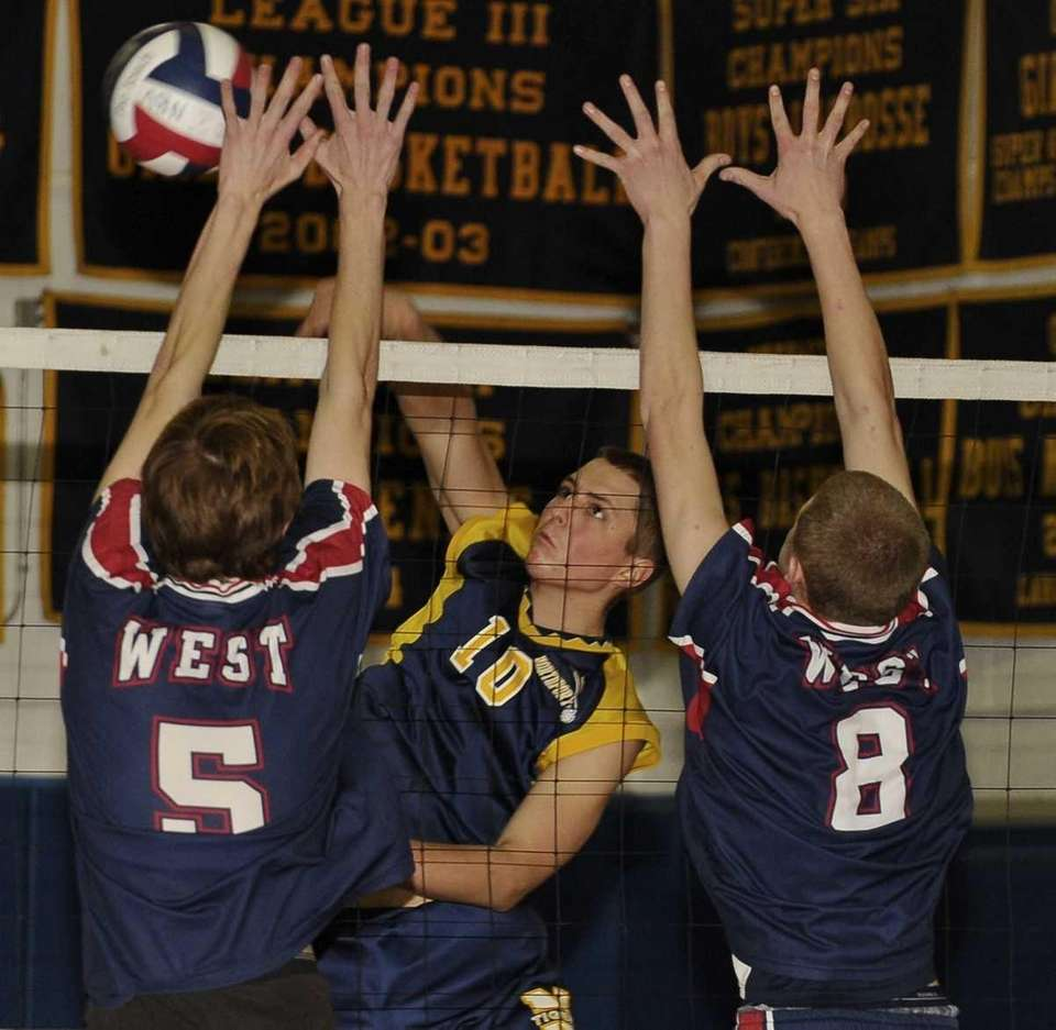Northport's Jeremy Thide spikes the ball past Smithtown