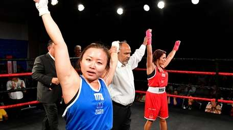 Referee Frank Pena raises the arms of Jane