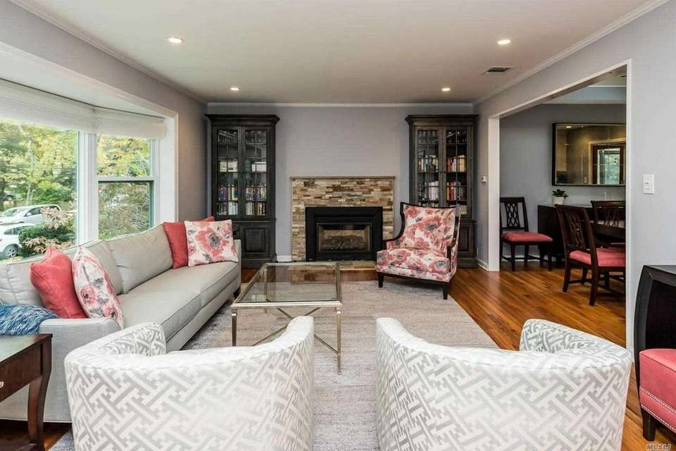 The living room, featuring a fireplace, opens to