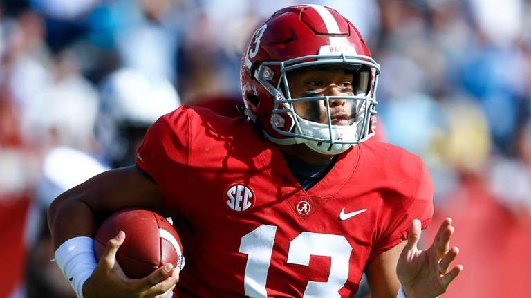 Alabama quarterback Tua Tagovailoa carries the ball during