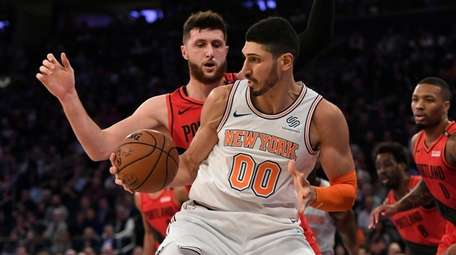 The Knicks' Enes Kanter dribbles the ball during