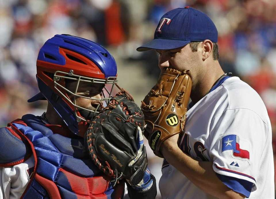 Texas Rangers starting pitcher Colby Lewis, right, confers