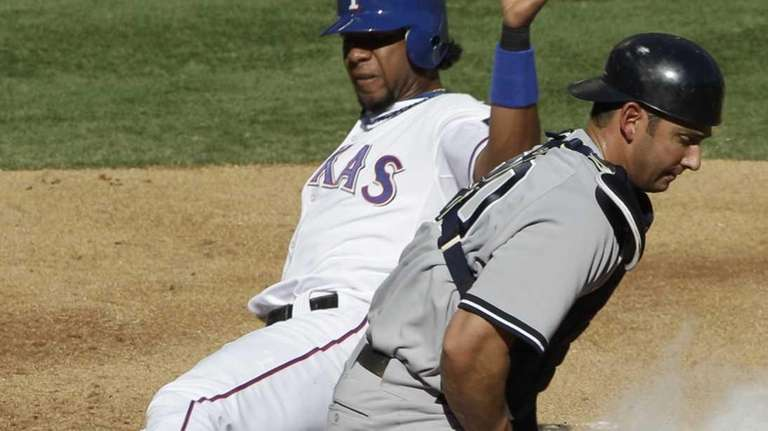 Texas Rangers' Elvis Andrus, left, slides home to