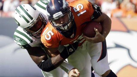 Denver Broncos quarterback Tim Tebow (15) is tackled