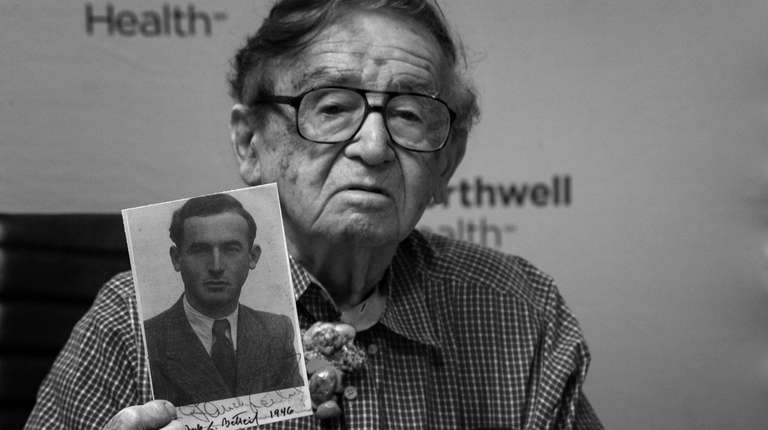 Betteil holds a photograph of himself in 1946,