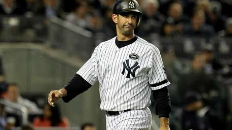 The Yankees' Jorge Posada walks back to the