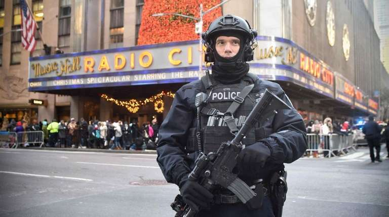 A heavily armed NYPD officer patrols the parade