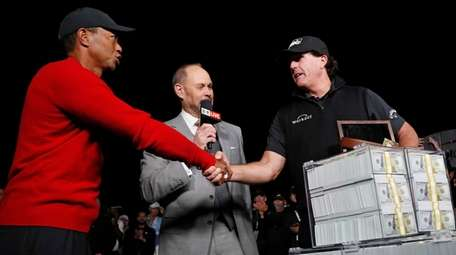 Tiger Woods, left, shakes hands after losing a