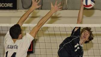 Massapequa's Christopher Husmann spikes the ball past Plainview's