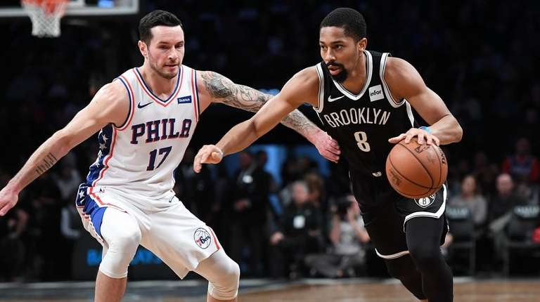 The Nets' Spencer Dinwiddie dribbles past the 76ers'
