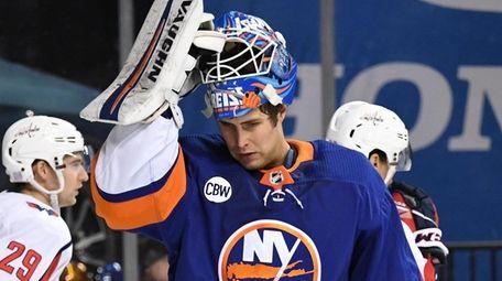 Islanders goaltender Thomas Greiss adjusts his helmet after