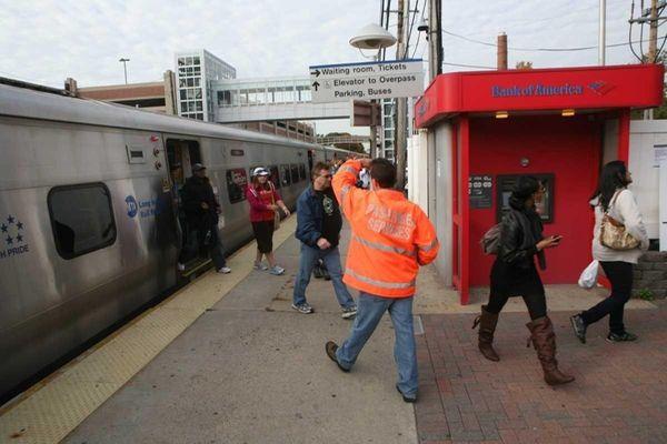 An MTA passenger service worker directs LIRR riders