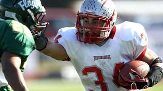 Connetquot's Mike Pellegrino (34) with the stiff arm