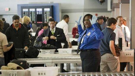 A TSA officer gives directions to passengers at