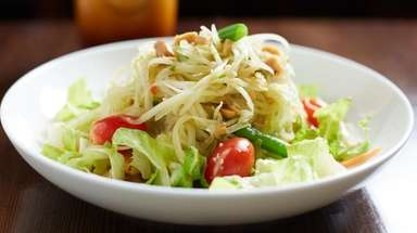 Spicy green papaya salad is served with ground