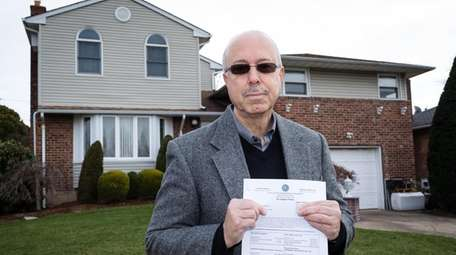 Cory Eisner, 63, holds his Nassau County tax