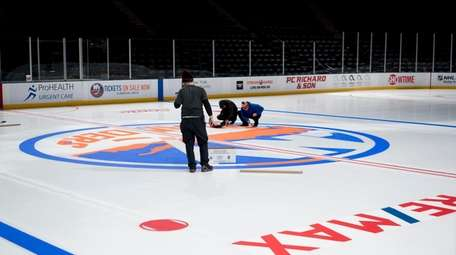 Coliseum workers paint the Islanders logo onto the