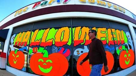 A man walks past a halloween store in