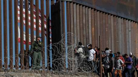 Central American migrants look through a border fence