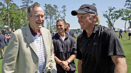 Former President George H.W. Bush, left, talks with