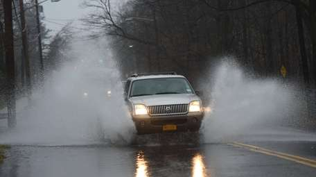 A vehicle navigates through minor street flooding on