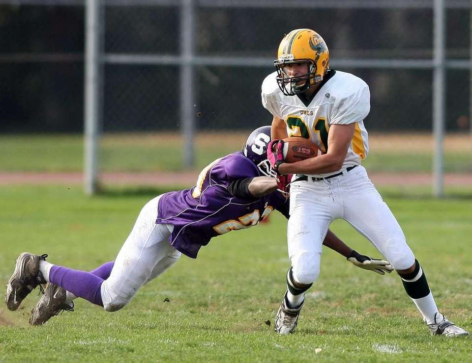 Lynbrook's #21 Luke Spitzer breaks a tackle attempt