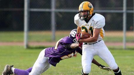 Lynbrook's #21 Luke Spitzer breaks a tackle attempt