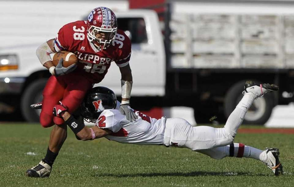 Bellport's Mike Burton breaks a tackly by Newfield's