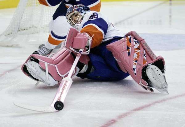 Islanders goalie Rick DiPietro tries to poke the