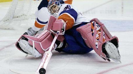 Islanders goalie Rick DiPietro tries to poke the