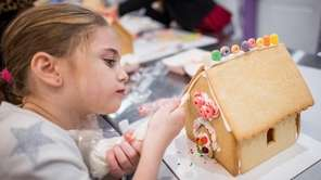 Emily Minetti works on a cookie house during