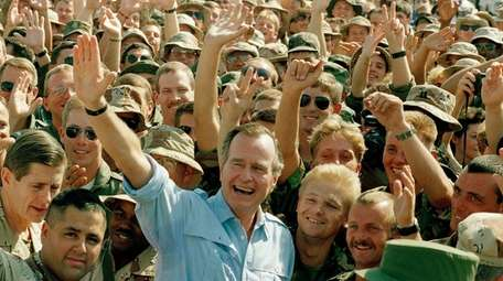 President George H.W. Bush visits with soldiers at