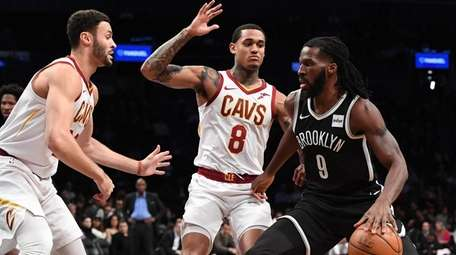 Nets' DeMarre Carroll is defended by Cavaliers' Larry