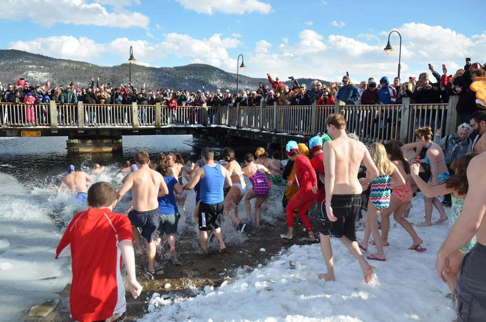 Participants in the polar plunge wade into a