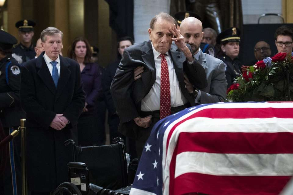 Former Sen. Bob Dole stands up from his