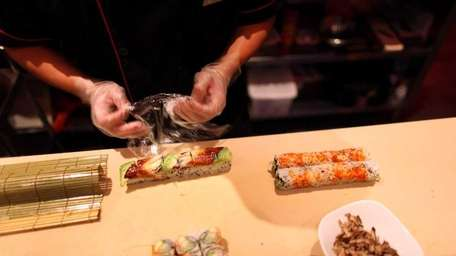 A sushi chef prepares an order at the