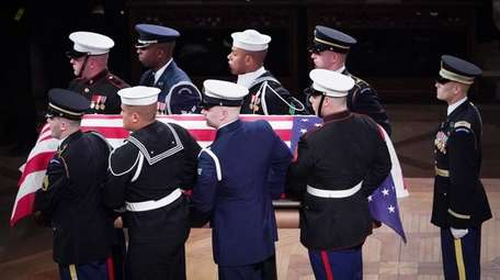 Pallbearers carry the coffin containing former U.S. President