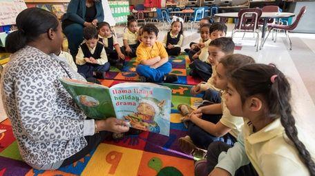 June Hicks, a pre-K teacher, reads a book