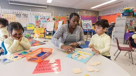 Pre-K teacher June Hicks works with two of