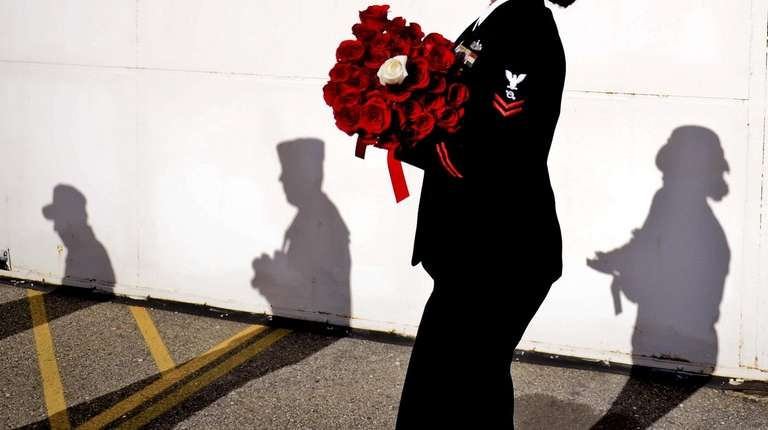 The U.S. Navy walks with blessed roses during